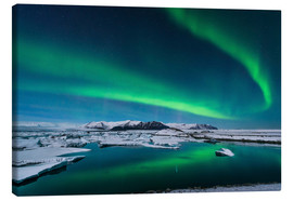 Tableau sur toile  The northern lights dance over the glacier lagoon in Iceland. - John Davis